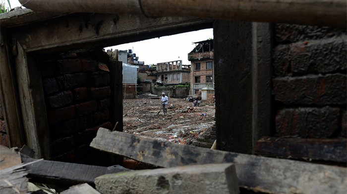 A nepalese man can be seen through a doorway of a collapsed house in Bhaktapur. Broken timber beams are in foreground