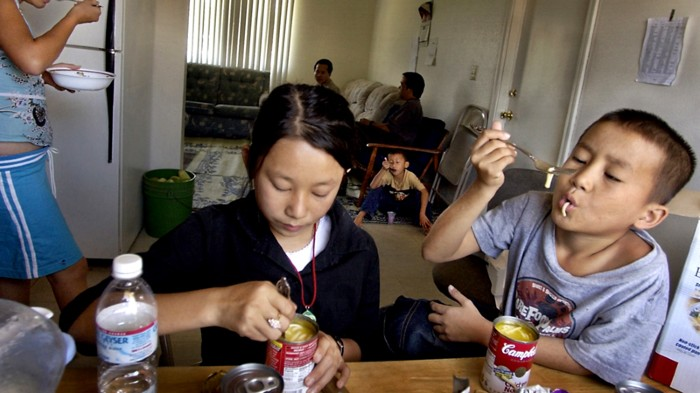 Hmong children eat soup from cans in Sacramento, California.