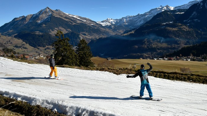 Tourists ski on a thin layer of snow in the Alps