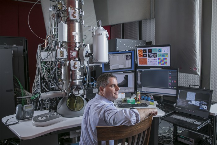 David Muller seated in front of his electron microscope in his lab at Cornell University