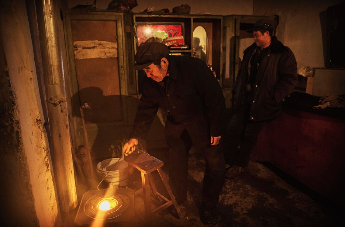 Chinese farmer stokes a coal stove