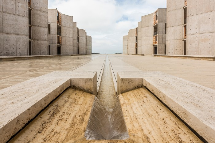 Open stone courtyard at the Salk Institute, with a perspective view of the water feature, and office buildings to either side