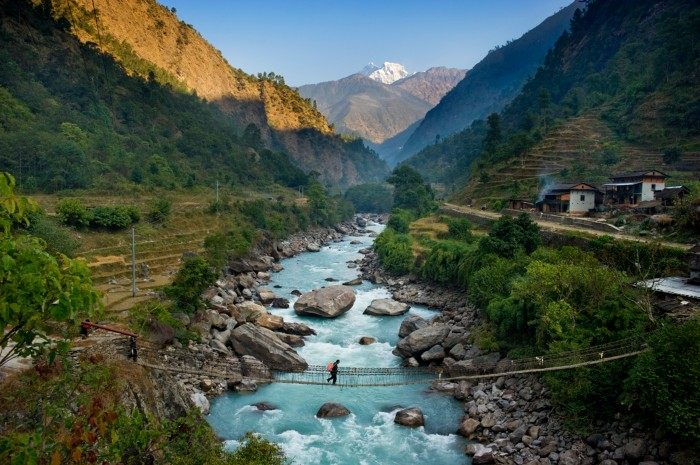 Un uomo che attraversa un ponte sospeso in Nepal
