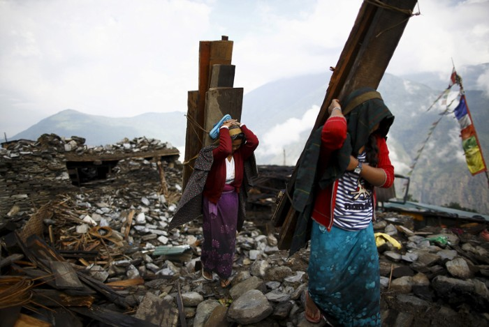 People salvage wood from house destroyed by the Gorkha earthquake, Nepal.