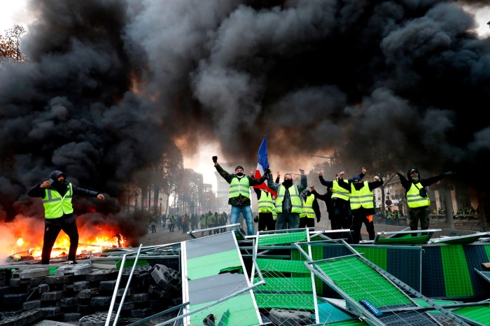 Yellow vests (Gilets jaunes) protestors shout slogans as material burns