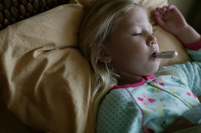 Girl sick in bed with thermometer