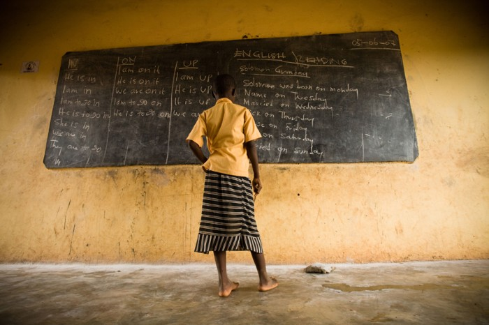 Girl standing at a blackboard at a primary school in Ghana