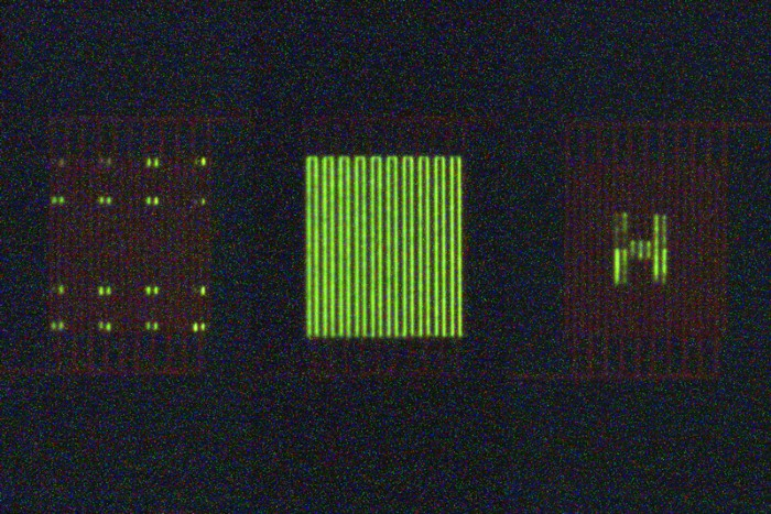 Three organic light-emitting transistors displaying different patterns of green light