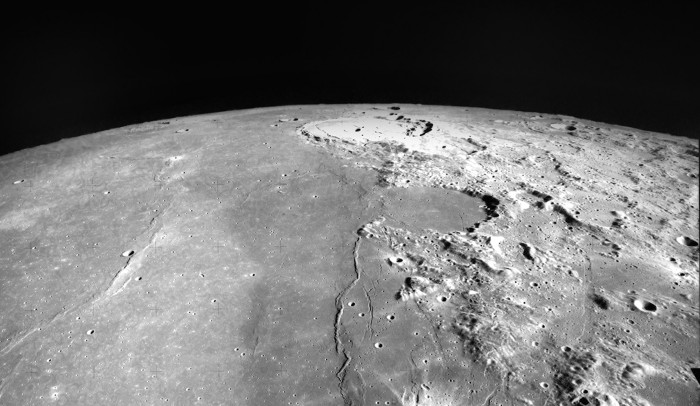 View of the Moon's horizon, with a flat plain on the left and a rocky landscape on the right.