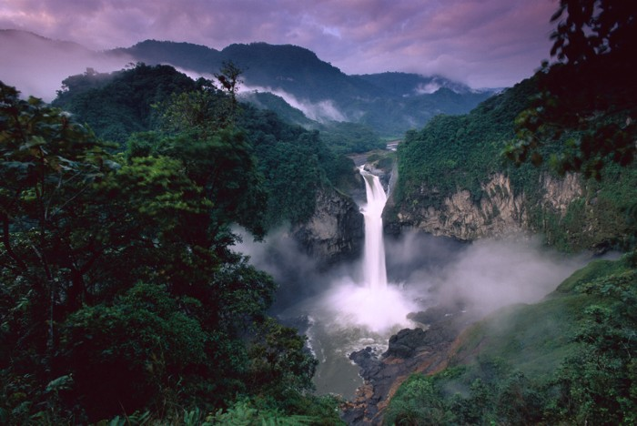 A large waterfall in the middle of a tropical rainforest with dark trees and a purple sky