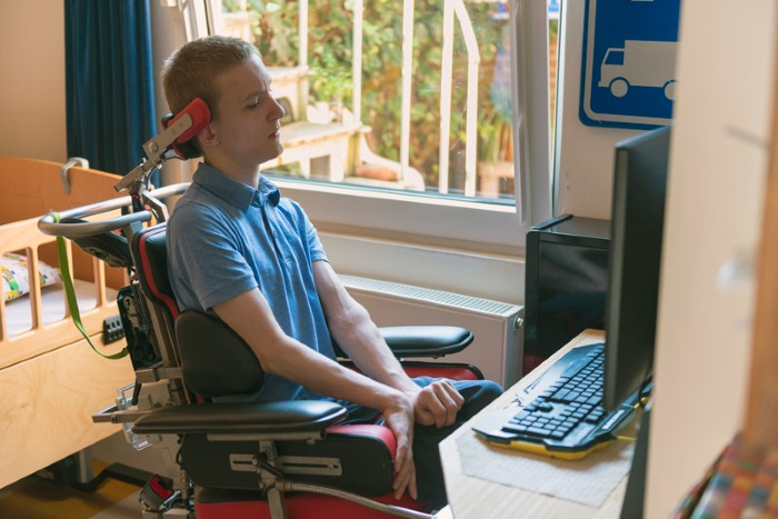 A young ALS patient playing computer games with the help of his electronic wheelchair