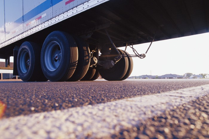 Rear wheels of a truck sitting on tarmac