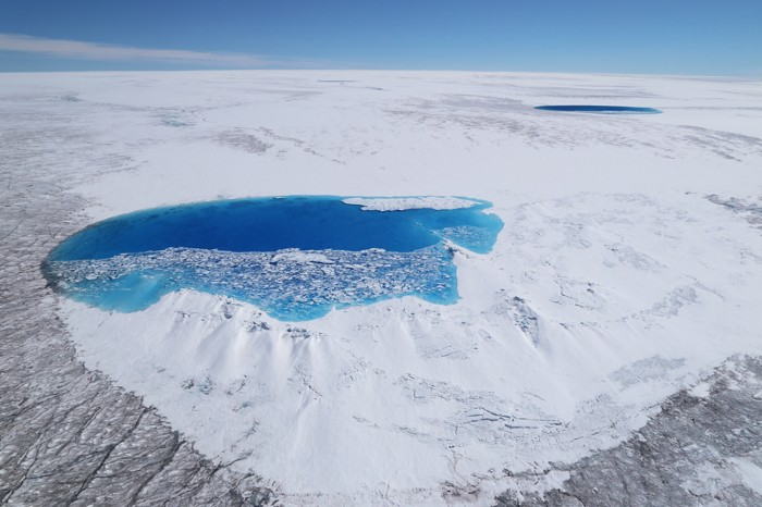 Aerial view of a melt pool and contrasting colours of the Greenland Ice Sheet