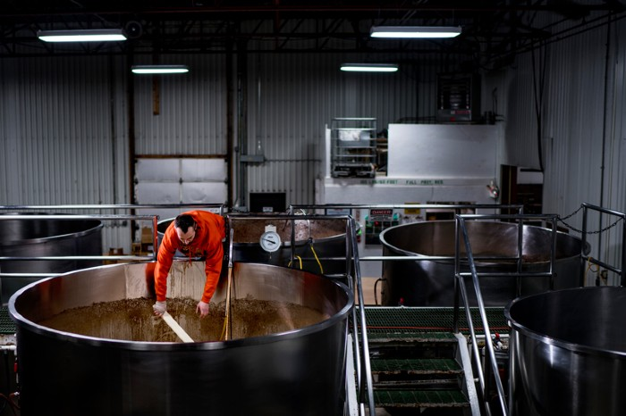 A worker leans into a large tank to remove yeast from beer during the brewing process
