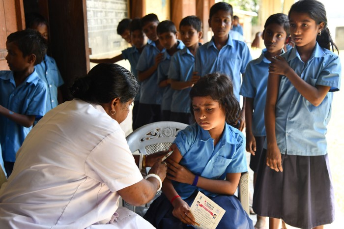 An India health worker injects a school pupil with a measles and rubella vaccine while other pupils wait to receive the vaccine