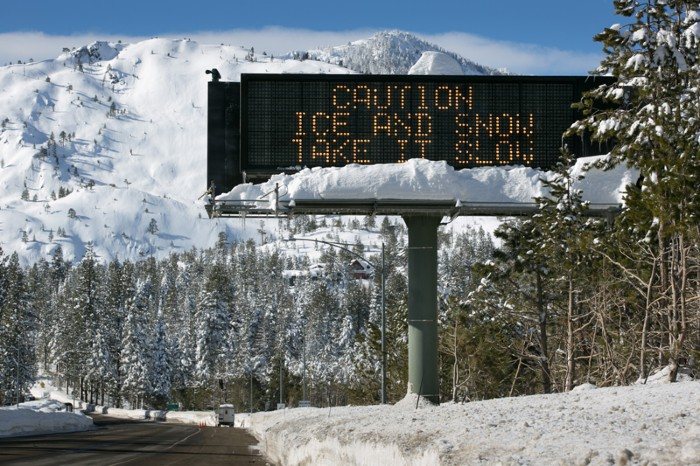 An electronic sign on a road in South Lake Tahoe warns of snow and ice