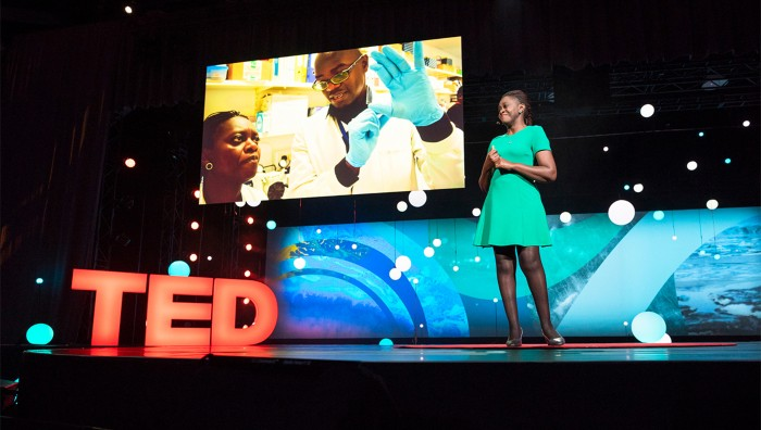 Faith Osier smiles while standing in front of LED screens during her TED presentation in Canada, 2018