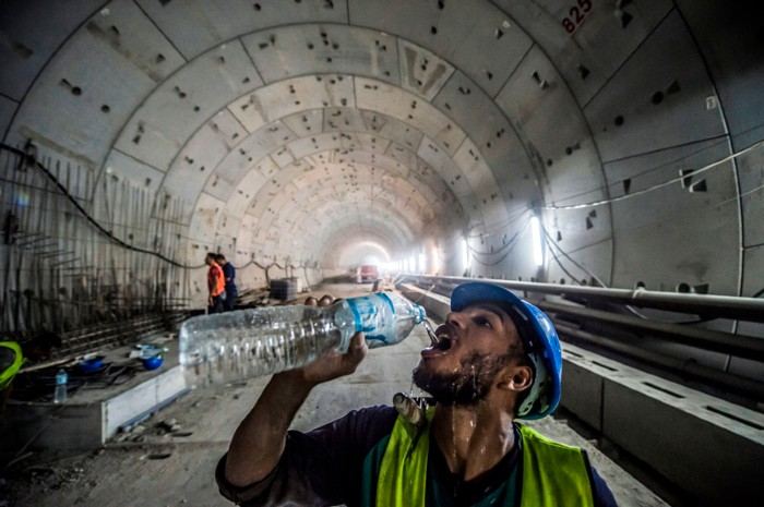 A construction worker drinks from a bottle of water at the site of a new road tunnel