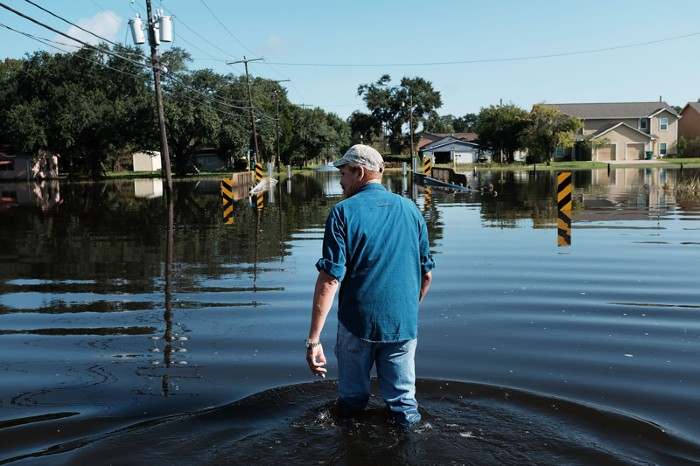 A man walks through knee-high flood waters in a Texas neighbourhood affected by Hurricane Harvey