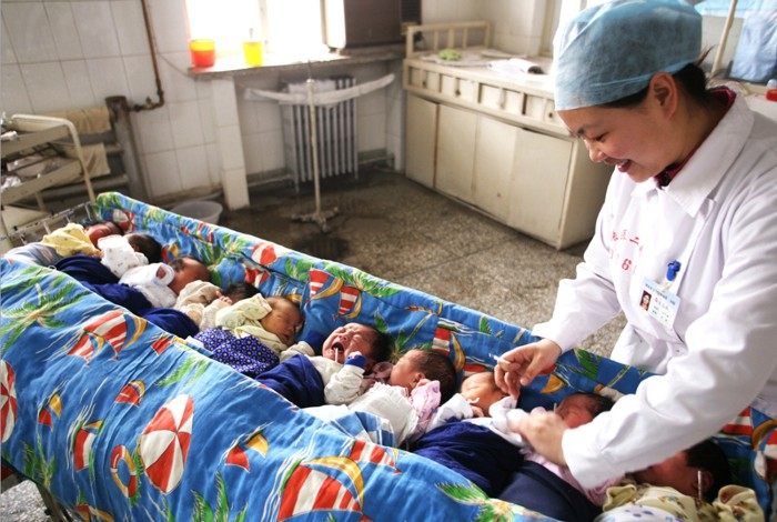 A nursing worker takes care of new-born babies at a hospital in China
