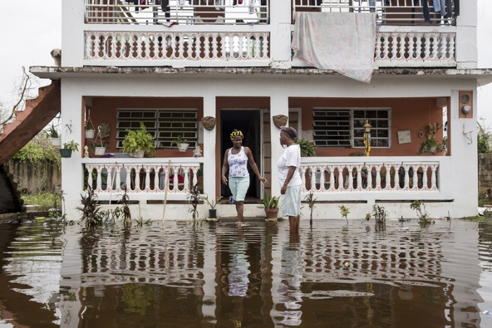 Residents wade through flood waters at their home days after Hurricane Maria made landfall in Puerto Rico