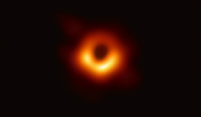 The first image of a black hole shows a bright ring formed by light bending in the intense gravity around the black hole.