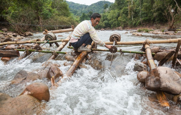 A man adjusts the propeller on a micro hydro turbine in the flow of the Nam Ou River at Ban Sop Kha, Laos.