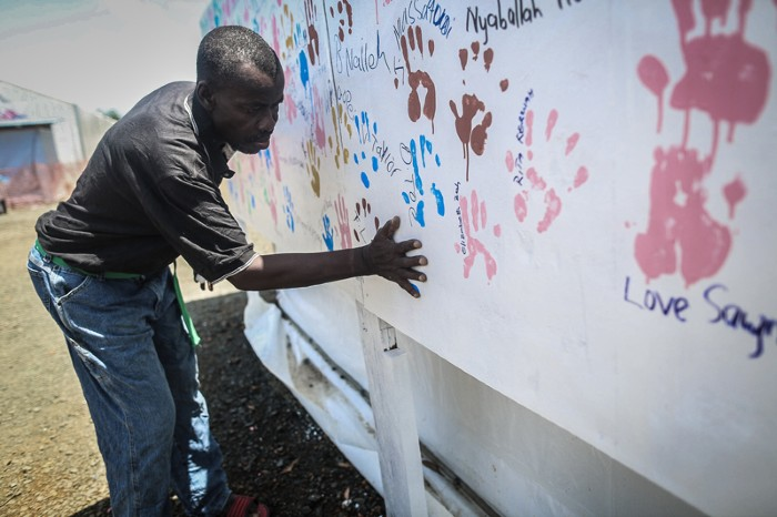 An Ebola survivor makes a handprint on a wall after being discharged from hospital, Liberia