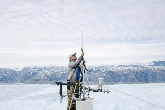 Researchers repairs a broken GPS module at a research station in Greenland