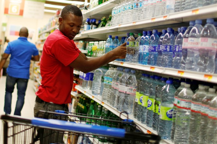 A supermarket employee puts water bottles on a shopping cart