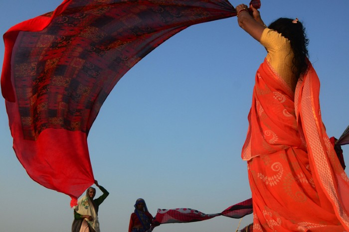 Indian women dry their sarees after taking a holy dip at Ganges river during a hot day in Allahabad