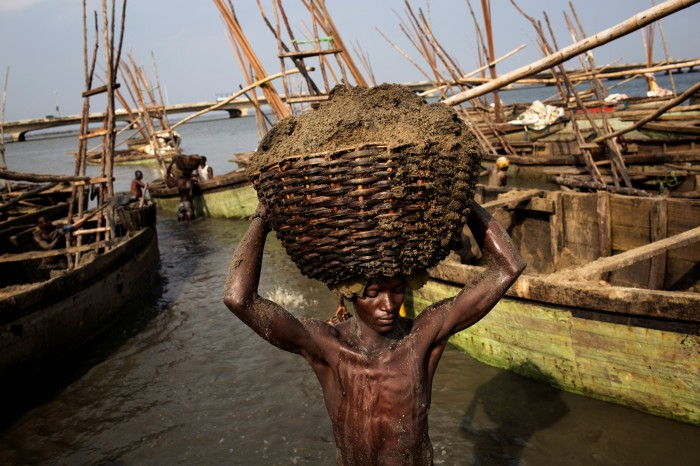A labourer carries away large basket of wet sand that has been dug from the seafloor of the Lagos Lagoon.