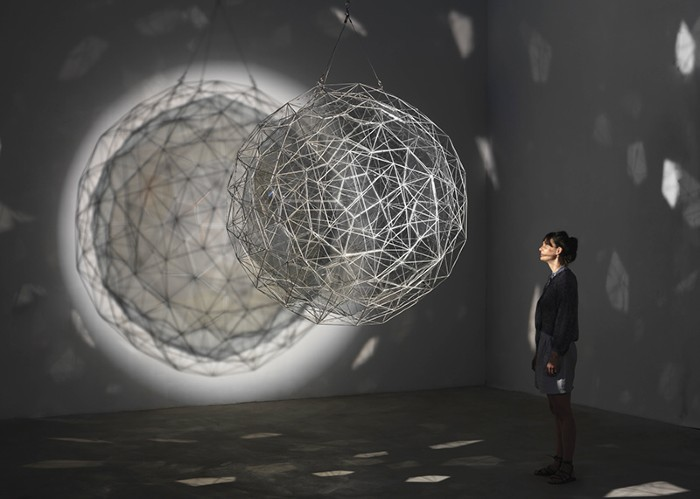 A woman in a darkened room looks at a ball of steel wire casting polyhedral shadows.