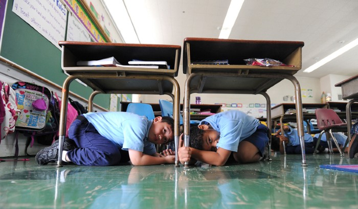 8th-grade students in Torrance, California, take cover under their school desks during an earthquake drill