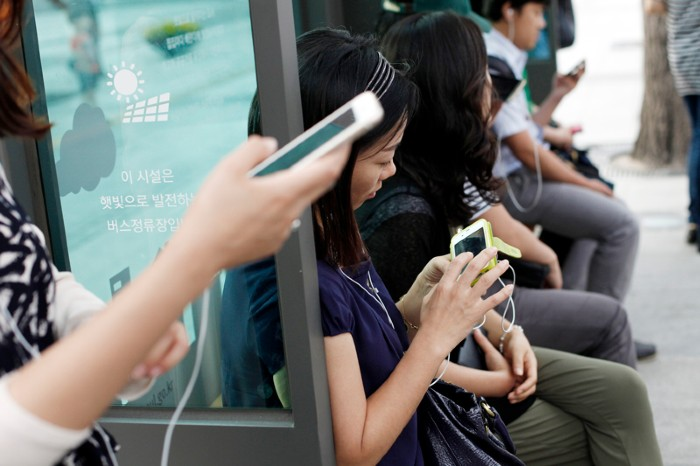 Passengers waiting at a bus station using smart phones