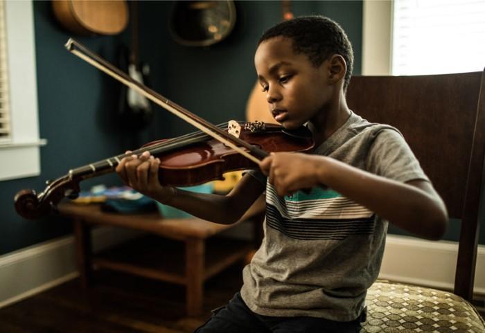 Young boy (6 yrs) practicing violin.