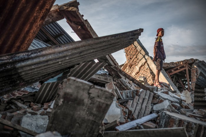 A resident stands on the ruins of a building that was destroyed by the earthquake on Palu, Indinesia