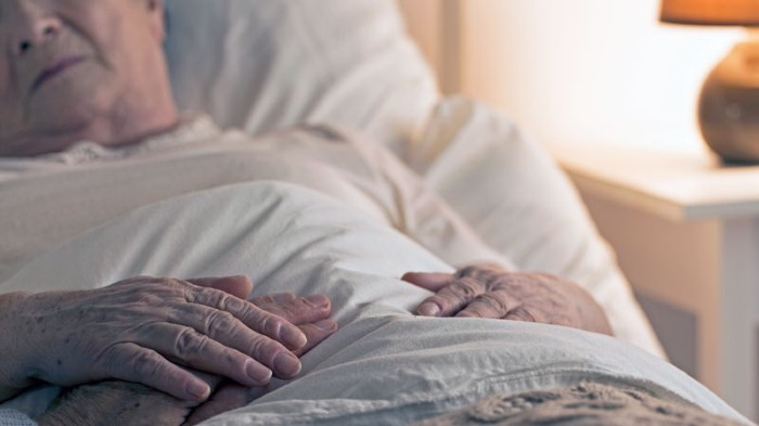 Close-up of hand of senior on hand of dying elderly person as sign of support during sickness.