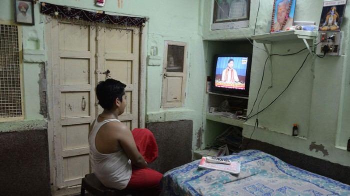 A man uses a television in his bedroom in Jodhpur, India.