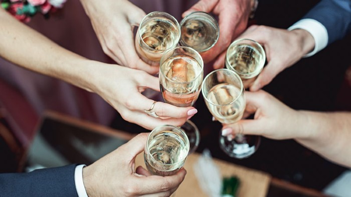 People hold in hands glasses with white wine and champagne above table.