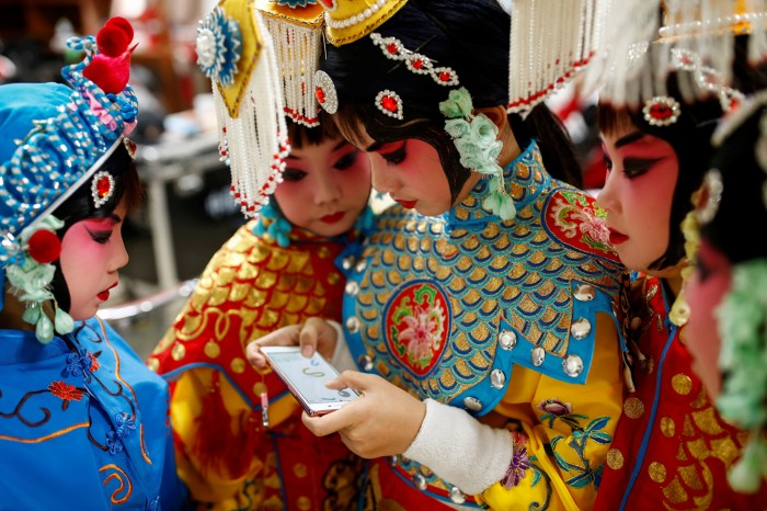 A teenage participant plays a game on her phone as others watch during a break in a traditional Chinese opera competition