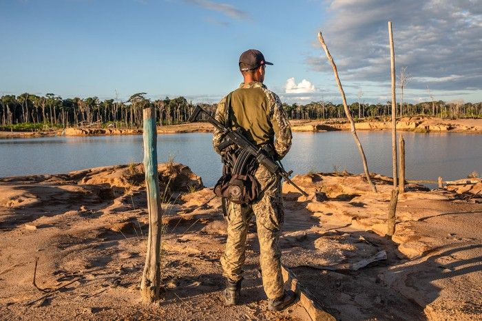 An armed Peruvian soldier looks over the remains of the La Pampa illegal gold mine