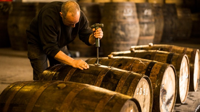 Worker opening wooden whisky cask in whisky distillery.