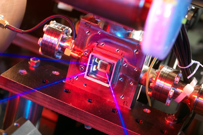 An ion trap on a microchip with lasers shining on it.