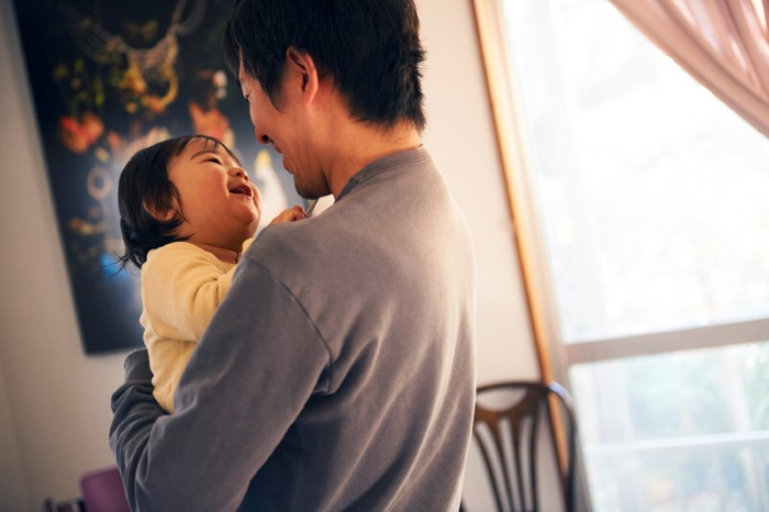 A father holds his infant daughter and smiles at her as she smiles back