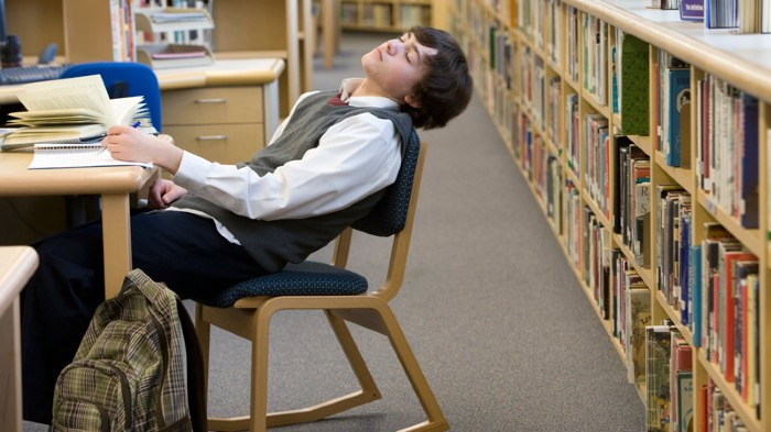 Teenager sleeping at desk in library.
