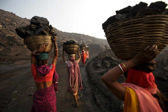 Women in brightly coloured traditional Indian dress carry large baskets full of coal on their heads