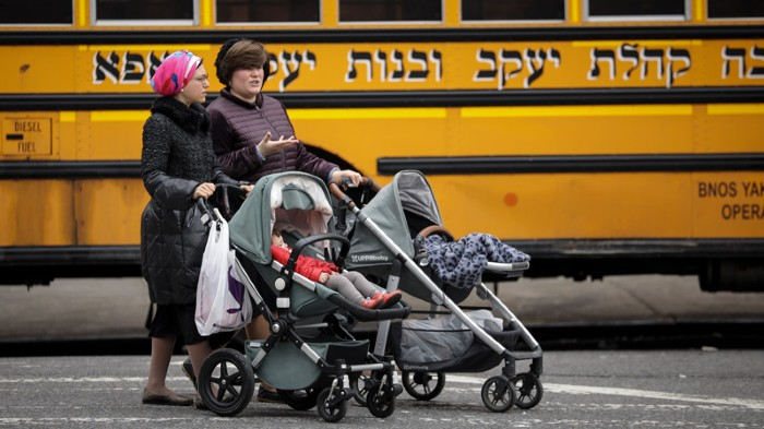 Women pushing strollers walk past the Yeshiva Kehilath Yakov School in the South Williamsburg neighborhood.