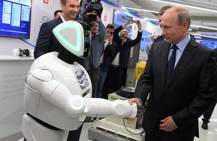 Vladimir Putin shakes hands with a robot at an exhibition by Russian businesses