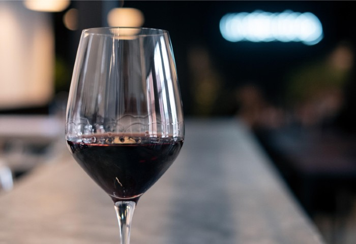Close-up of a glass of red wine on a bar counter.